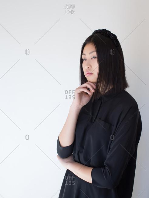 Pretty stylish Asian woman posing in studio