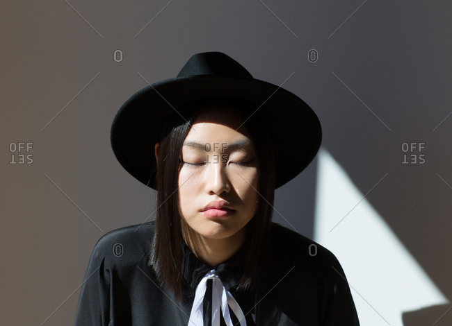 Stylish Asian woman with eyes closed