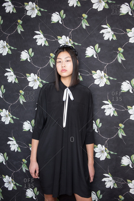 Pretty young Asian woman in black dress looking at camera and posing on background with flowers
