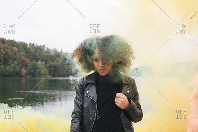 Young woman with colored smoke bombs