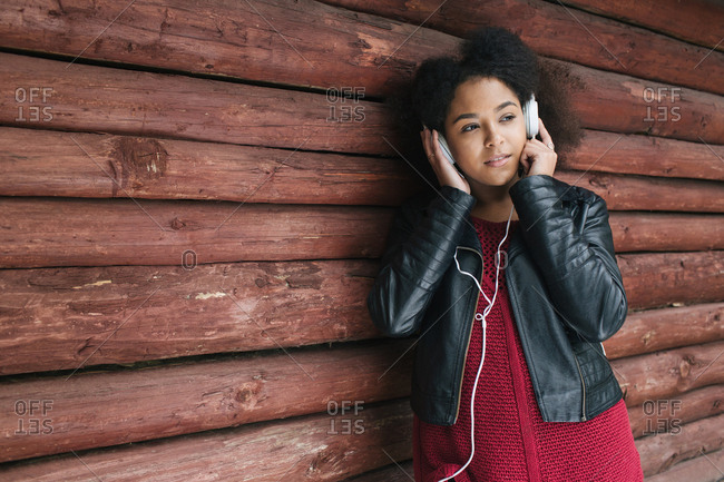 Young African-American woman standing near wooden wall and listening to music