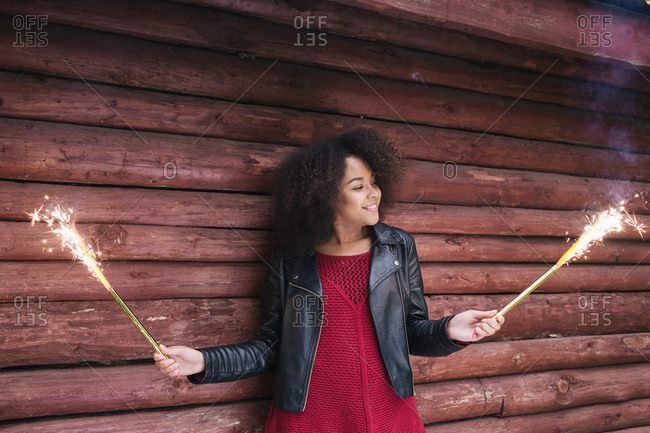 Young African-American woman in leather jacket standing near wooden wall and holding sparklers