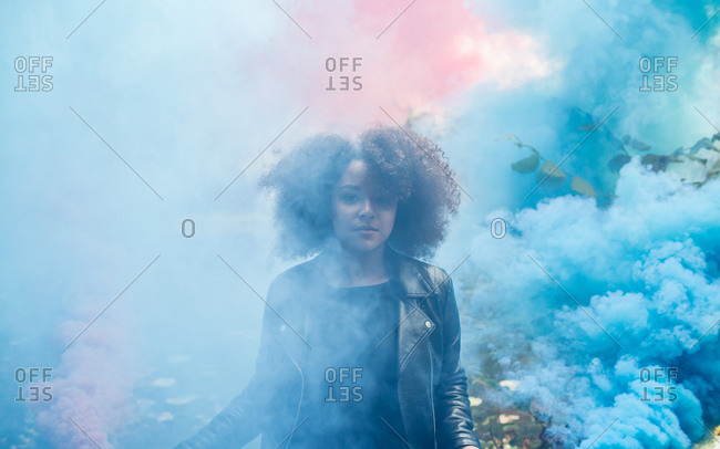 Young woman with colored smoke bombs stock photo - OFFSET
