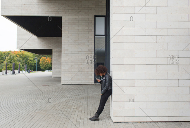 Young woman with smartphone near building
