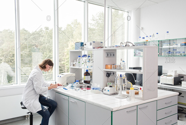 Woman writing in laboratory