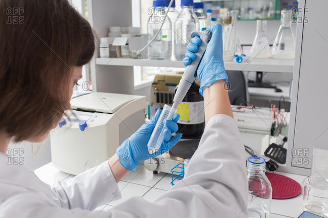 Woman working in laboratory and putting liquid to test tube in laboratory