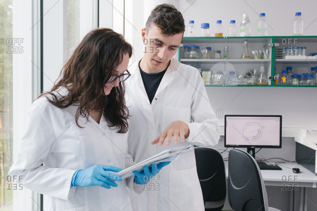 Young man and woman standing in laboratory and doing paperwork together