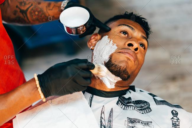 Hands of unrecognizable barber putting on shaving foam on face of black customer