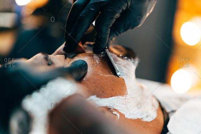 Barber shaving beard of customer