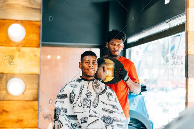 Barber showing haircut to customer