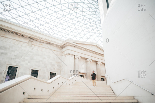 Man standing on white stairs in amazing museum with beautiful classical architecture in white color