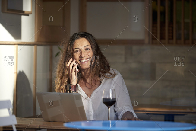 Woman drinking wine and using laptop