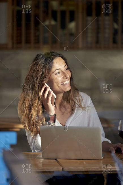 Woman drinking wine and talking on phone