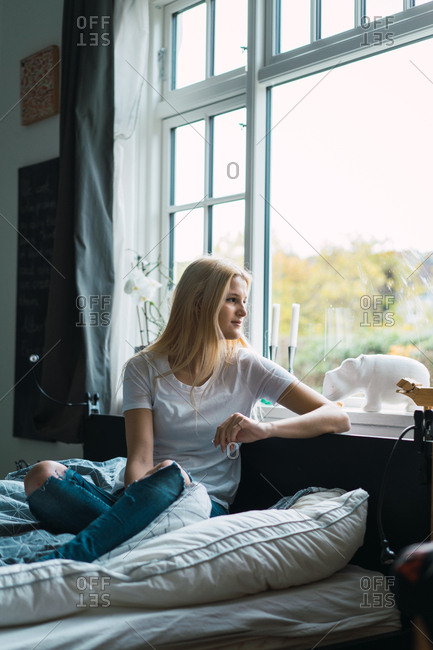 Young pretty blonde woman sitting on bed and looking away at window
