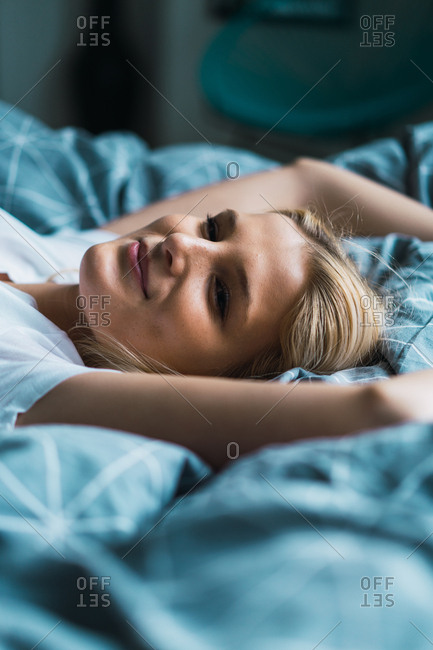 Delighted blonde young woman lying and relaxing in bed at home