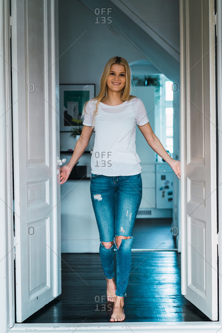 Smiling pretty young blonde woman posing in doorway at home