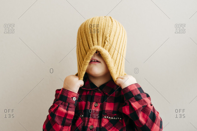 Cute boy covering face with wool cap