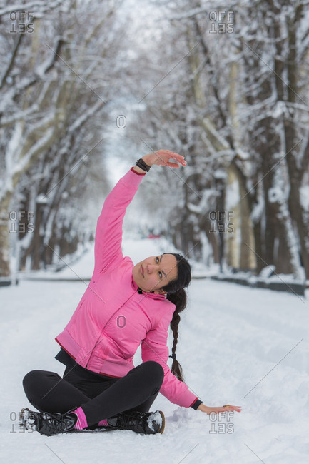 Young woman practicing yoga in snow