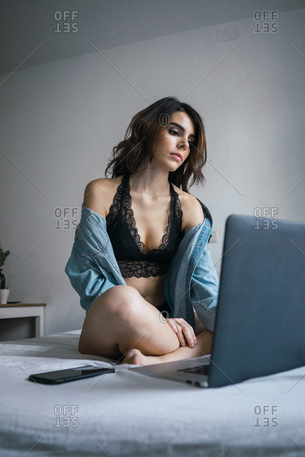Young woman in lingerie using laptop