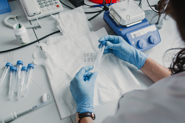 Hands of unrecognizable woman holding plastic test tube in laboratory