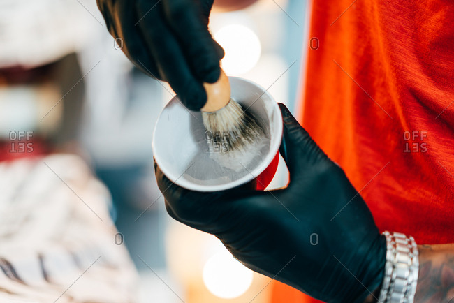 Hands of unrecognizable black barber making foam with brush in the bowl