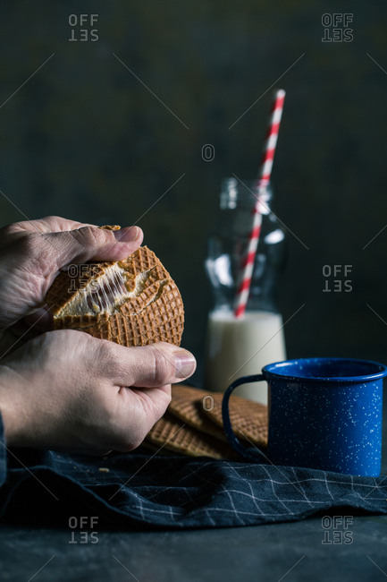 Toffee waffle biscuits with milk on dark background