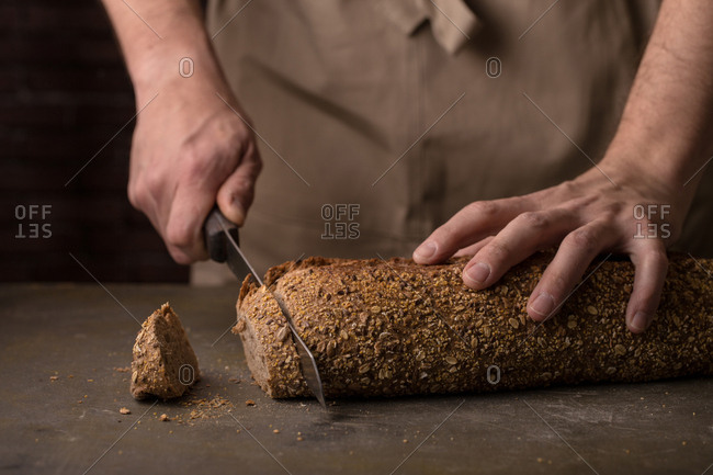 Man cutting a freshly baked loaf of bread