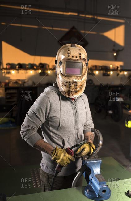 Professional mechanic working in a custom motorbike workshop