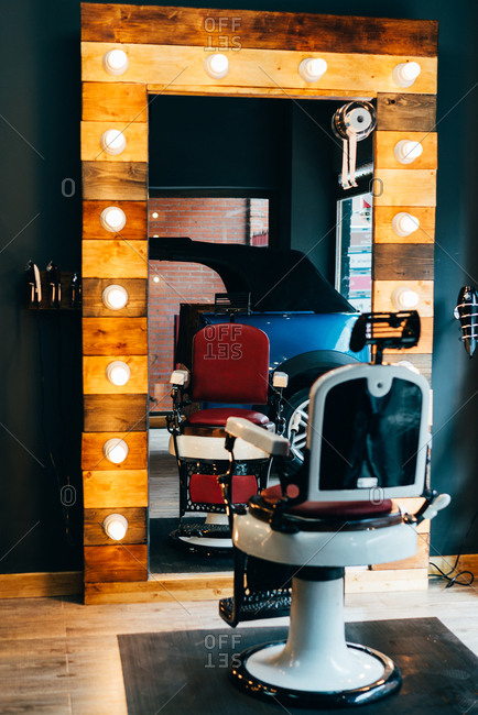 Empty chair placed at mirror with illumination in barbershop