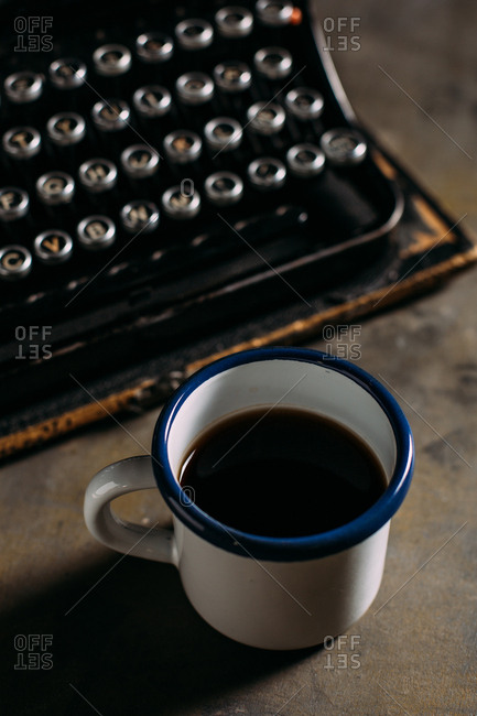 Enamel cup with coffee and retro typewriter