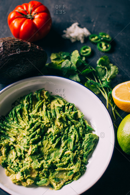 Preparing guacamole with avocado, tomato, onion lime and coriander