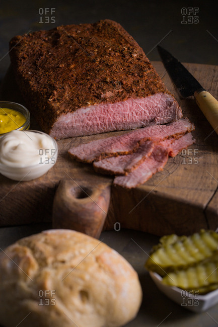 Sliced homemade pastrami ready with mayo, mustard, pickles and bread
