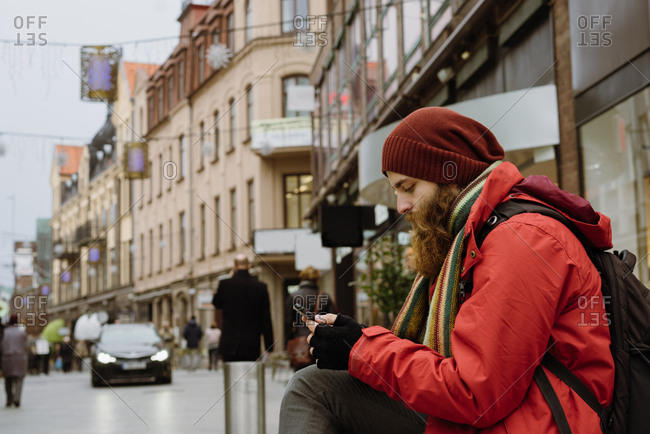 Bearded man using smartphone in city