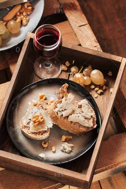 Appetizer in a tray with cheese, bread and wine