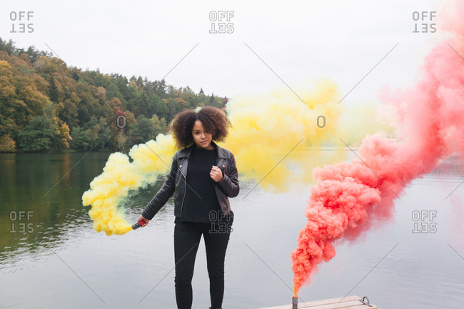 Young African-American woman in leather jacket standing on pier and holding colored smoke bomb