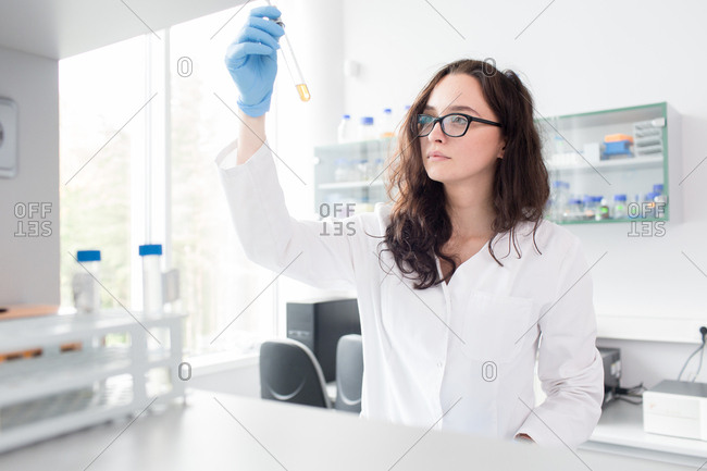 Woman in whites and glasses looking at reaction in test tube in laboratory