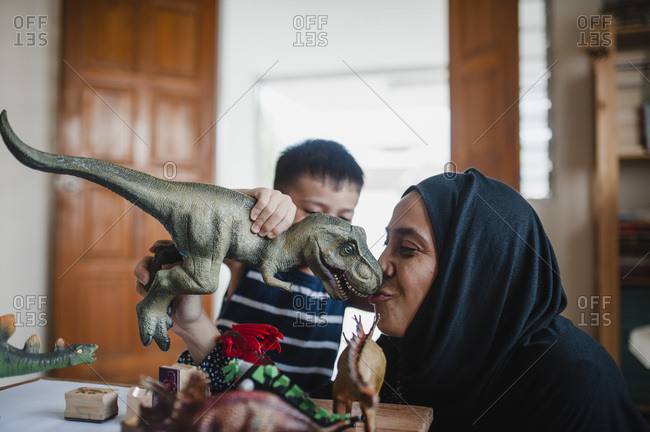 Mother and son playing with dinosaurs together