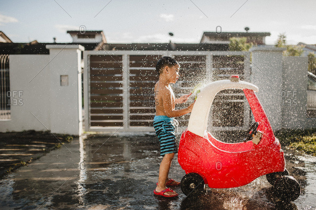 Boy washing his toy car outside