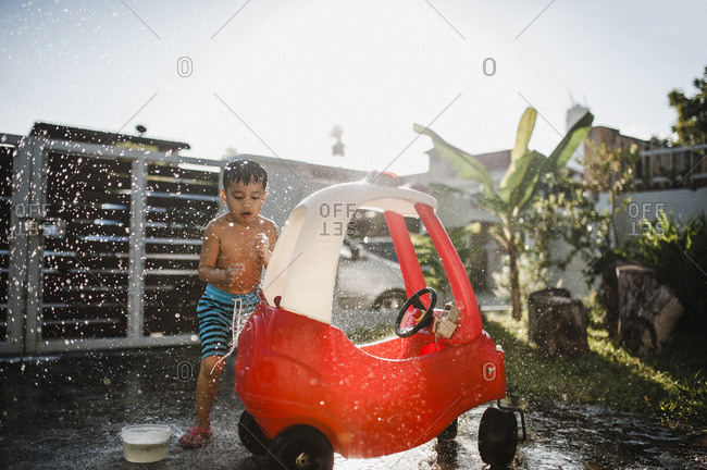 Boy cleaning his toy car outside