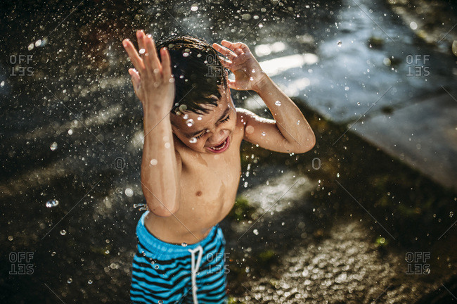 Little boy playing in splashing water outdoors