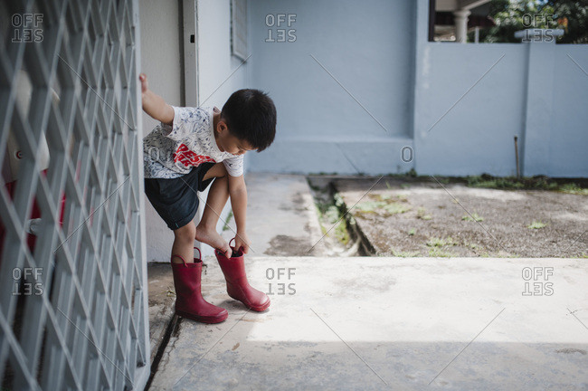 Little boy getting on rain boots