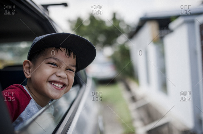 Happy little boy looking out window of a car