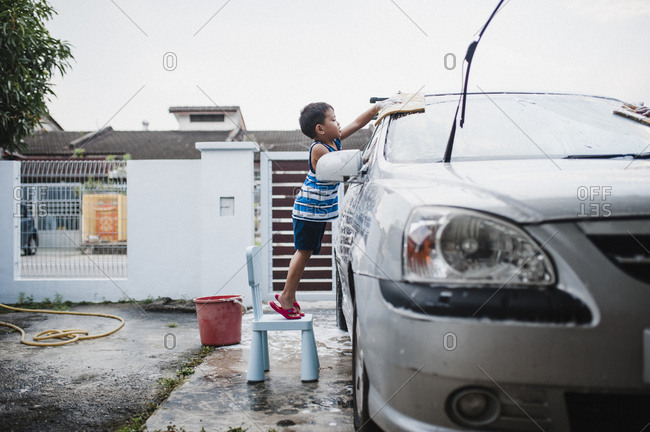 Boy standing on chair washing car