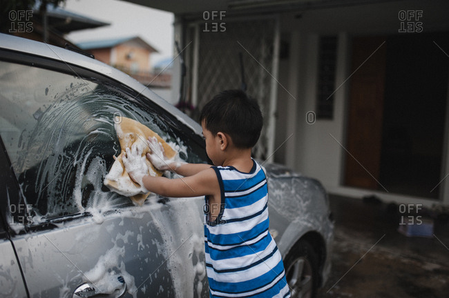 Boy washing car with soapy sponge