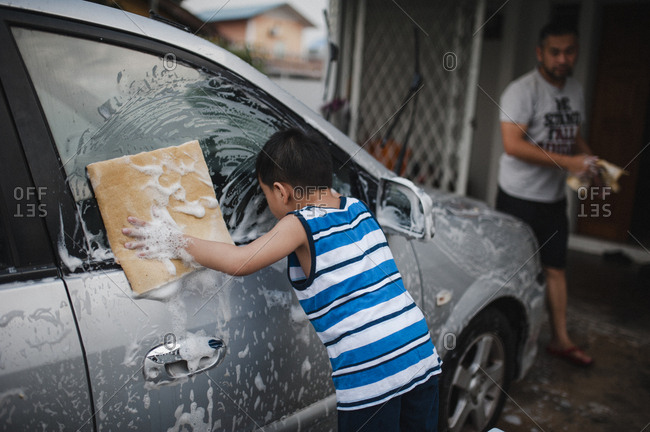 Little boy and his dad washing a car