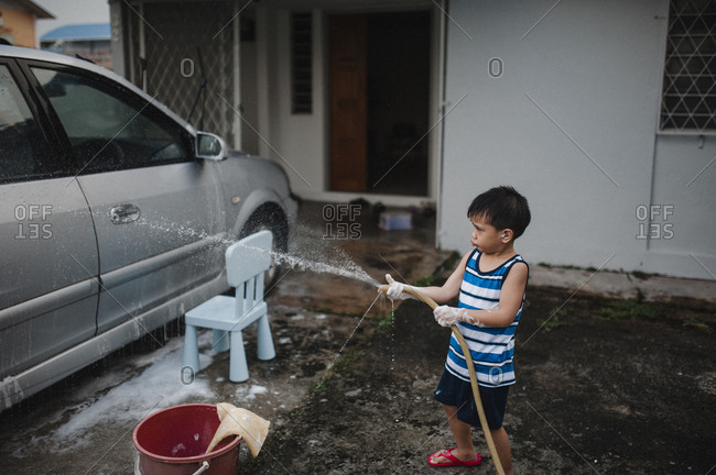 Little boy washing car with soap and a garden hose