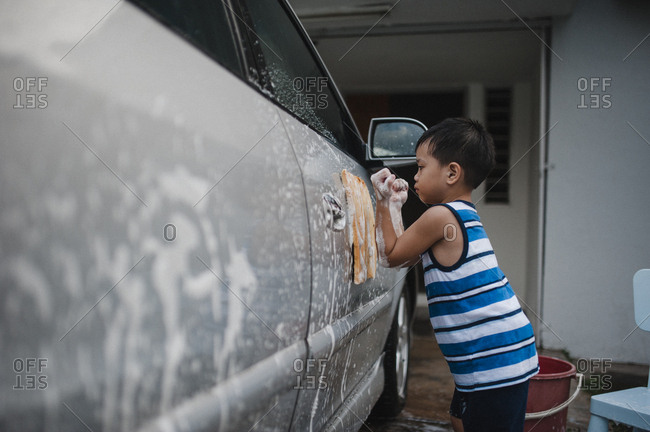 Young boy washing car with soapy sponge