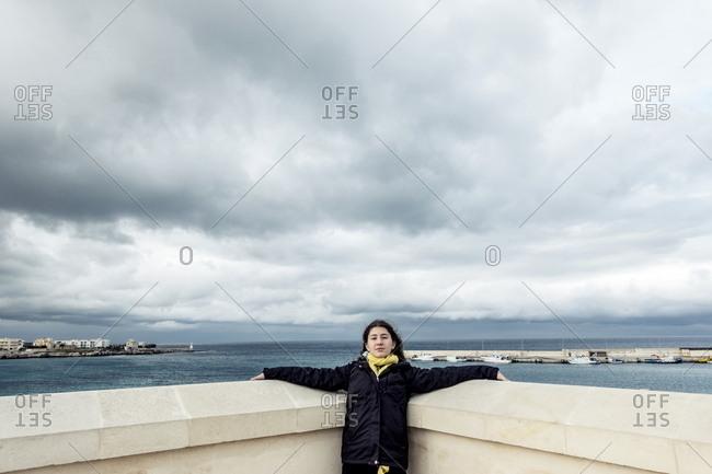 Girl traveler posing in corner wall at oceanside attraction