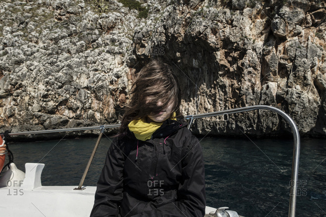 Girl with windswept hair in her face on boat ride