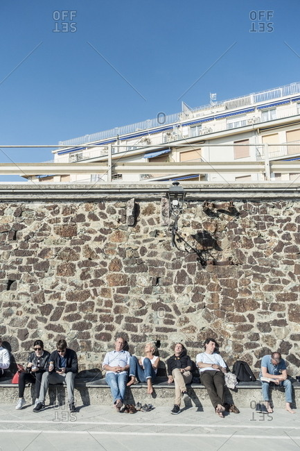 Levanto, Italy - April 4, 2017: People relaxing in the sun in the coastal town of Levanto, Italy